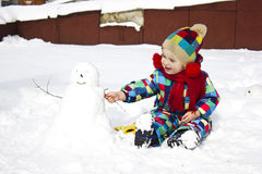 Little girl with snowman Royalty Free Stock Photo