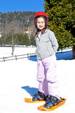 Little girl with snowshoes and the helmet Stock Photo