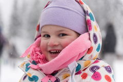 Little girl at snowy winter day Stock Images