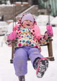Little girl at snowy winter day swing in park Royalty Free Stock Photo