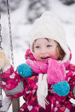 Little girl at snowy winter day swing in park Stock Images