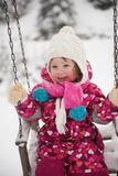 Little girl at snowy winter day swing in park Stock Photo