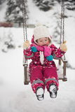 Little girl at snowy winter day swing in park Royalty Free Stock Photos