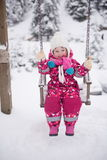Little girl at snowy winter day swing in park Stock Photos