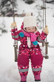 Little girl at snowy winter day swing in park Stock Image