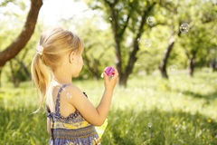 Little girl with soap bubbles Stock Image