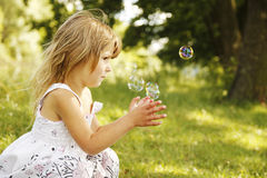 Little girl with soap bubbles Stock Images