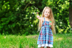 Little girl with soap bubbles in the park Stock Images