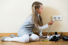 Little girl with socket extender and charging units indoors Stock Photography