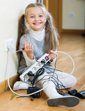Little girl with socket extender and charging units indoors Royalty Free Stock Image