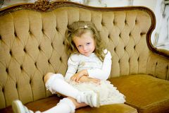 The little girl on a sofa. The little girl in a beautiful white dress poses on a sofa. It has on the head a rim with a small crown royalty free stock photo