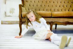 The little girl on a sofa. The little girl in a beautiful white dress poses on a sofa. It has on the head a rim with a small crown royalty free stock images