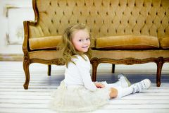 The little girl on a sofa. The little girl in a beautiful white dress poses on a sofa. It has on the head a rim with a small crown stock photos