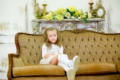 The little girl on a sofa. The little girl in a beautiful white dress poses on a sofa. It has on the head a rim with a small crown stock photography