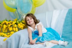 The little girl on the sofa with a bouquet of flowers. Royalty Free Stock Photo