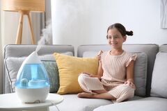 Little girl on sofa in room with modern air humidifier