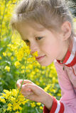 The little girl Sofia on the yellow plant Stock Photo