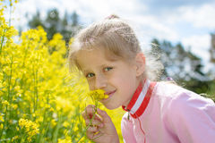 The little girl Sofia on the yellow plant Royalty Free Stock Photos