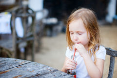 Little girl with a soft drink. Adorable little girl drinking with a straw a soft drink royalty free stock photography