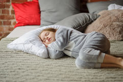 Little girl in a soft pajamas has fallen asleep waiting for something. Royalty Free Stock Photo