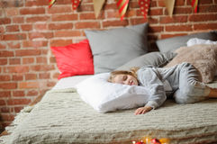 Little girl in a soft pajamas has fallen asleep waiting for something. Royalty Free Stock Images