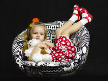 A little girl with a soft toy on a chair Royalty Free Stock Photography