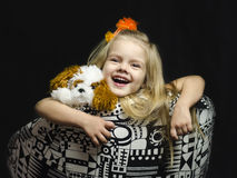 A little girl with a soft toy in the chair. Stock Photo