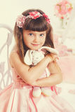 Little girl with soft toy sitting on a chair Stock Photo