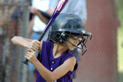 Little girl with softball helmet up to bat. Little girl at bat with batting helmet on Royalty Free Stock Photography