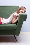 Little girl softly sleeping on a green sofa Stock Photo