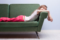 Little girl softly sleeping on a green sofa Stock Image