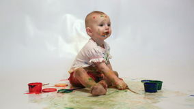 Little girl soiled by multi-colored paints sees stock video
