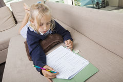 Little girl solving mathematics sums on sofa Royalty Free Stock Photo