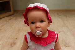 Little Girl with soother. little baby with a pacifier. in a white and pink dress and hat, sits on the floor and looks at the camer. Little Girl with soother stock photo