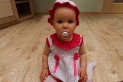 Little Girl with soother. little baby with a pacifier. in a white and pink dress and hat, sits on the floor and looks at the camer. Little Girl with soother stock image