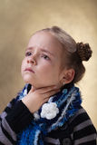 Little girl with sore throat in flu season. Touching her neck Royalty Free Stock Image