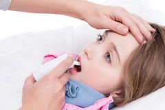 Little girl with sore throat using spray. Little girl with sore throat lying in bed and using spray on white background Stock Image