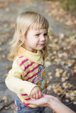 Little girl with a sour face taking candy from the mother's hands. Royalty Free Stock Images