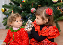 The little girl in the Spanish suit shows to the one-year-old little sister a toy about a New Year tree Stock Photos