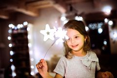 Little girl with a sparkler at Christmas time. Beautiful little girl with a sparkler at Christmas time at home Royalty Free Stock Photo