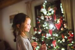 Little girl with a sparkler in front of Christmas tree. Beautiful little girl with a sparkler in front of Christmas tree at home Stock Photos