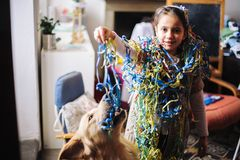 Little girl with sparklers around her neck and head for the carnival party in her house plays with her dog. Little girl with streamers around the neck and head royalty free stock photos