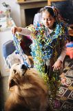 Little girl with sparklers around her neck and head for the carnival party in her house plays with her dog. Little girl with streamers around the neck and head stock photos