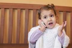 Little girl speaking by cell phone Stock Image