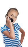 Little girl speaking by cell phone, white Stock Image