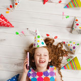 Little girl speaking by mobile phone to your friends on birthday Stock Image