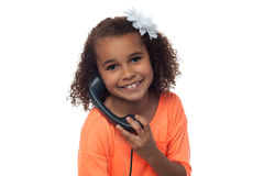 Little girl speaking over phone Stock Photos