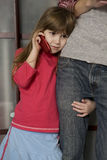 Little girl speaking by phone. Girl standing at her father Royalty Free Stock Image
