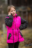 Little girl speaks by mobile phone while standing outdoors. Communication. Royalty Free Stock Images