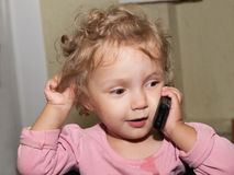 Little girl speaks by phone Royalty Free Stock Photos